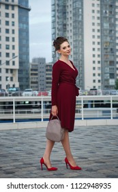 Young attractive girl in red dress and high-heeled shoes. She holds a handbag in her hands.