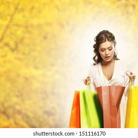 Young attractive girl with the shopping bags over autumn background