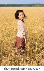 Young attractive girl standing in wheat field