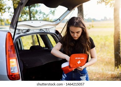Young attractive girl stands near car with open back door and emergency light is on, tries to find something in first aid kit. Concept of car crash and giving first aid