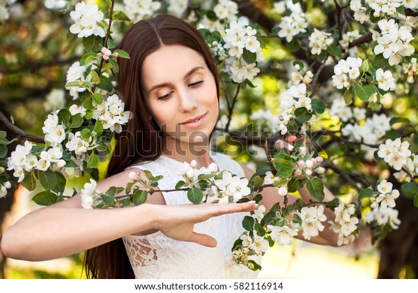 Young attractive girl with straight long hair standing in flowering Apple orchards. Beauty smiling woman looking at white flower