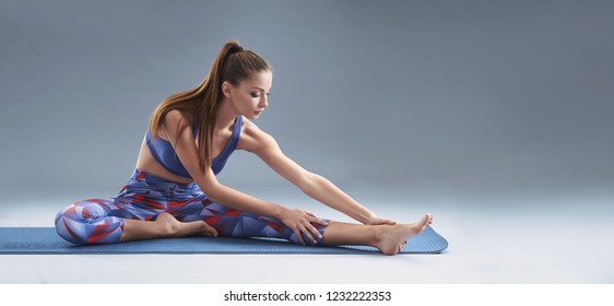 Young attractive girl stretches on yoga mat. Beautiful slim brunette practicing gymnastics exercises. Solid background, copy space. Banner and mock up concept