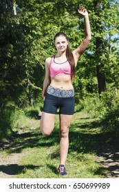 Young, attractive girl stretches in woods before jogging.