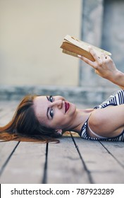 Young attractive girl studying and reading a book on a wooden floor . Relax, rest, education concept, recreation.