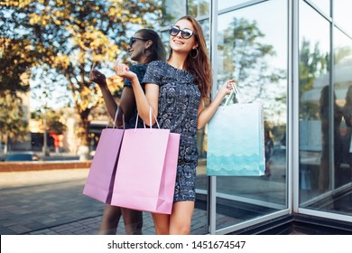 Young attractive girl in sunglasses enjoying a good shopping in the city , with bags in hand