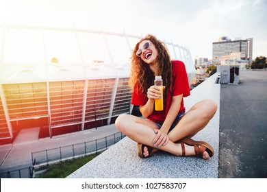 Young attractive girl in sunglasses holds a bottle with fresh juice, cheerfully smiling, enjoying a sunny day while sitting on marble slab , in a city.
