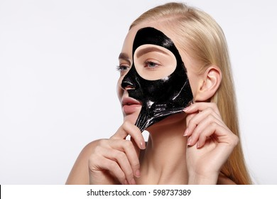 Young attractive girl takes off black facial face.