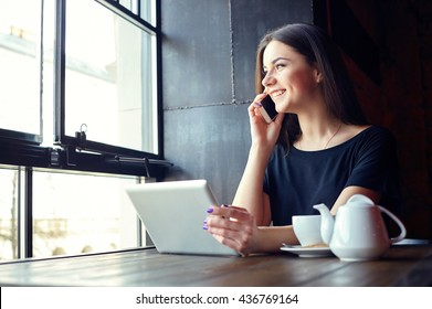 Young attractive girl talking on mobile phone and smiling while sitting alone in coffee shop during free time and working on tablet computer. Happy female having rest in cafe. Lifestyle