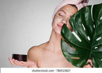 young attractive girl with a towel on her head, put on her face a coffee scrub, holds a green leaf