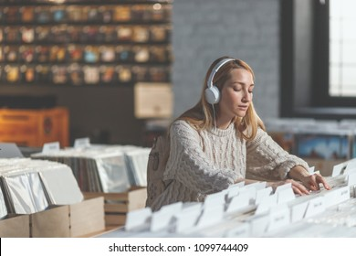 Young attractive girl in a vinyl record store