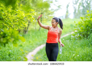 Young attractive girl waving to a friend during her jogging in the park, holding a bottle of water. Smiling girl waving hand