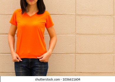 young attractive girl wearing a orange t shirt standing on brick wall background, copy space.