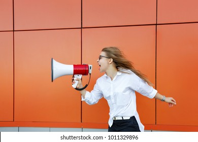 A young attractive girl in a white shirt and glasses is holding a loudspeaker in her hands. She screams into the megaphone. Protest. The struggle for equality.