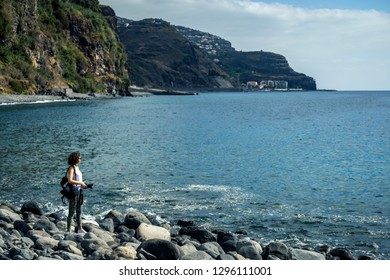 Young and attractive girl in white shirt and sneakers is sitting on the rocky beach on Madeira's island. Beautiful landscape on background. Sunny day.