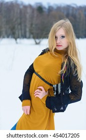 Young attractive girl in yellow dress posing on winter snowy glade