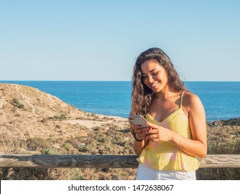 young and attractive girllooking at the smartphone with the sea behind with the evening light