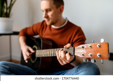 Young attractive guy with an acoustic guitar in a cozy home atmosphere. Concept hobby, creativity, music, talent