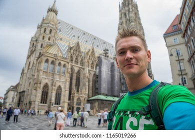 young attractive guy with blue eyes taking selfie with huge church on background in europe