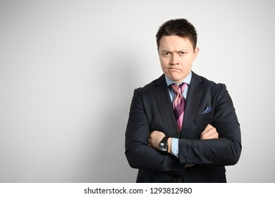 Young attractive guy businessman in suit on gray with skeptic expression nervously standing.