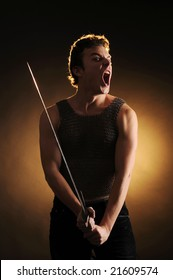An young attractive guy holding a sword in hands