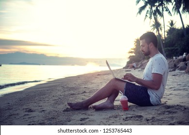 Young attractive guy a man with a beard sitting on the beach with a laptop on the background of the sea and sunset, distant work, freelancer, blogger, vacation and travel