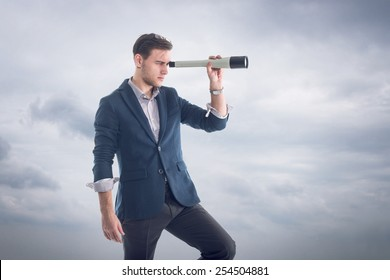 Young attractive handsome businessman standing  with clouds around and looking through the spyglass to find new perspectives