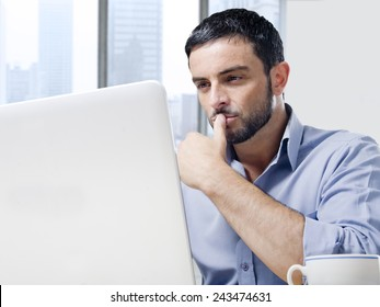 Young attractive and handsome businessman working on computer laptop with coffee cup sitting at office desk in front of skyscraper window view looking concentrated