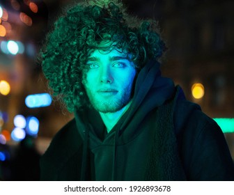 Young, attractive, handsome curly boy poses on a green neon background. Street, urban modeling, portrait, fashion photo. Cyberpunk style photography with high fashion model. Green Neon light.