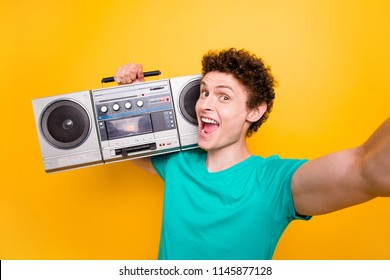 Young attractive handsome funky curly-haired excited guy wearing casual green polo t-shirt listening loud music, holding boombox. Isolated over bright shine vivid yellow background