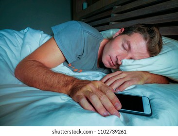young attractive and handsome tired man on his 30s or 40s in bed sleeping peacefully and relaxed at night holding mobile phone in internet social media addiction concept and smart phone overuse