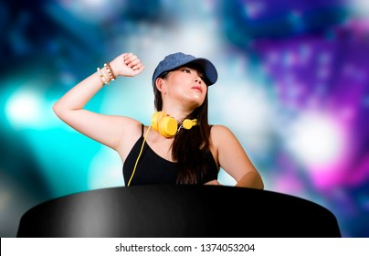 young attractive and happy Asian Japanese DJ woman remixing techno music using deejay gear and headphones at night club with lights background in clubbing fun and night lifestyle concept