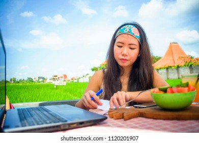young attractive and happy Asian Korean digital nomad working outdoors relaxed with laptop computer writing notes in success job as online social media travel blogger