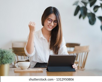 Young attractive happy Asian woman using tablet with success business deals, excited by good news, woman sitting at coffee shop raising hand in yes gesture celebrating business success.