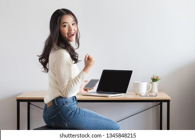 Young attractive happy Asian women using laptop and smartphone with excited posture.