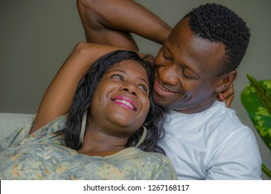 young attractive and happy black afro American couple relaxed at home sofa couch cuddling sweet enjoying together and smiling in man and woman in love enjoying beautiful relationship