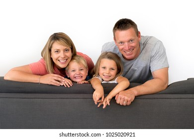 young attractive and happy couple posing sitting at home sofa couch holding their beautiful little daughter and adorable 3 years old son smiling playful in family lifestyle concept