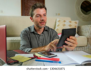 young attractive and happy freelance business man with calculator and laptop doing domestic accounting paperwork of domestic payments taxes and monthly money income sitting at home
