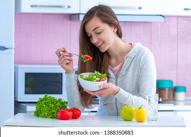 Young attractive happy healthy woman in sportswear eating fresh vegetable salad at home in kitchen. Balanced organic diet and clean fitness eating.