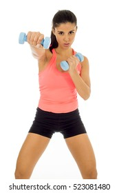 young attractive happy latin woman in sport clothes with beautiful smile holding weight dumbbell doing fitness workout isolated on white background in healthy lifestyle concept
