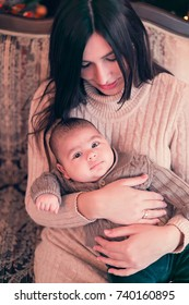 Young attractive happy mother have a good time with her son at home near christmas tree. Family, happiness, holidays, new year concept