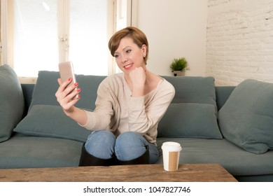 young attractive and happy red hair woman sitting at home sofa couch drinking coffee taking selfie picture with mobile phone camera in internet social media addiction and lifestyle concept
