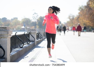 young attractive and happy runner woman in Autumn or Winter sportswear running and training on jogging outdoors workout in urban park in fitness and healthy lifestyle concept