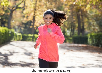 young attractive and happy runner woman in Autumn sportswear running and training on jogging outdoors workout in city park with trees and yellow leaves in fitness and healthy lifestyle concept