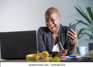 young attractive and happy successful black afro american woman in business jacket working cheerful at office laptop taking notes using mobile phone satisfied in work success concept