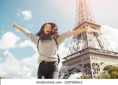 Young attractive happy woman jumping for joy against Eiffel Tower in Paris, France. Portrait of travel tourist girl on vacation walking happy outdoors. Gorgeous mixed race Asian Caucasian female