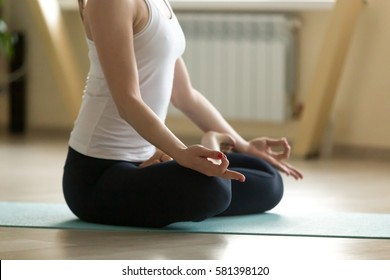 Young attractive happy woman practicing yoga, doing Padmasana exercise, Lotus pose with mudra, working out, wearing sportswear, white tank top, indoor full length, home or sport club, closeup