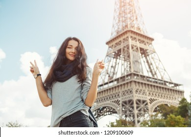Young attractive happy woman showing peace gesture Eiffel Tower in Paris, France. Portrait of travel tourist girl on vacation walking happy outdoors. Gorgeous mixed race Asian Caucasian female