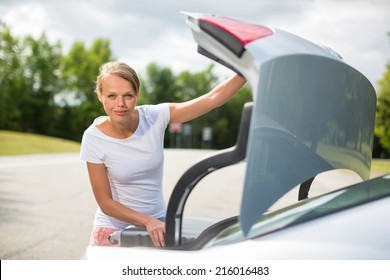 Young, attractive, happy woman taking a suitcase from her car's trunk, smiling, enjoying the travel experience