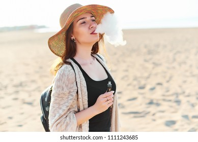 Young attractive happy woman wearing straw hat vaping electronic cigarette and blowing smoke on sunny summer day on the beach. Travel and tourism concept.