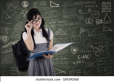 Young attractive high school student studying at class while looking at camera